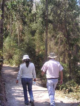 Two people walking down a gravel path in the woods with their backs to the camera. The person on the left is wearing a white shirt, jeans, and a white bucket hat. Their brown hair is in a ponytail. This person may be Mariza. The other person has a pink shirt, jeans, and a brown bucket hat.