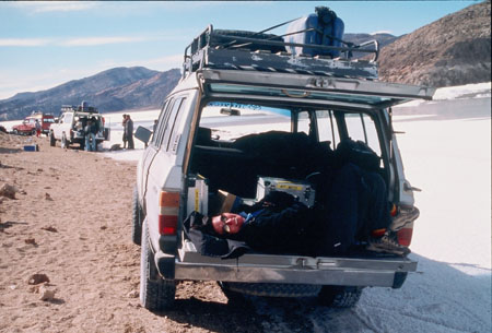 Kate is lying in the trunk of a green truck/SUV. She is wearing a black jacket, jeans, and sunglasses. There is a black jacket under her head. She is smiling into the camera. There are gray trunks behind her. There is a white SUV and a red SUV ahead on the terrain. People are outside the vehicles.