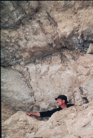Ken is behind a layer of rocks with a rocky wall behind him. He is wearing a black long sleeved shirt and black baseball cap. He is facing towards his right- the image's left- and reaching it.