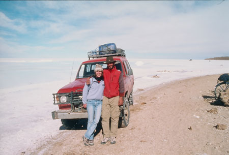 There is a red truck/SUV on a salty terrain. Tiffiny and someone else are leaning against the hood. Tiffiny is wearing a gray jacket, jeans, and a gray winter hat. The other person is wearing a red jacket, khaki pants, and a green cowboy hat.