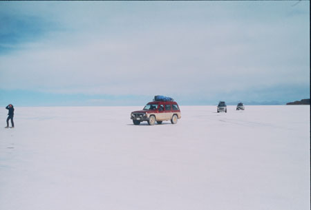 A red adn tan truck/SUV is driving across a salt plain. There are two cars behind it. There is someone in all black standing before the red truck.