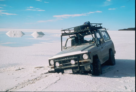 A gray truck/SUV's front right wheel is completely sunk into the salt terrain.