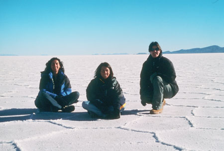 Kate and Tiffiny are sitting on the salty ground. Kelda is crouching on the right. There are hexagon patterns in the ground. Kate is wearing a blue jacket and jeans. She has shoulder length curly brown hair. Tiffiny is wearing a black jacket and jeans. She has shoulder length brown hair. Kelda is wearing a black jacket, jeans, and sunglasses. She has chin length brown hair.