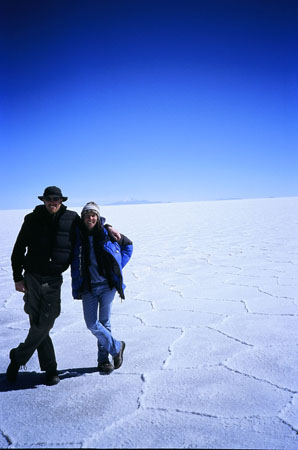 Ken and Tiffiny are standing on the salt plain. There are small ridges making different shapes on the ground. Ken (left) is wearing a blakc jacket, pants, sunglasses, and bucket hat. Tiffiny is wearing a blue jacket, jeans, and a gray winter hat.