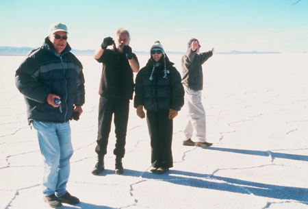 Les, Peter, Angela, and another person (left to right) are standing on the salt plain. Les is wearing a blakc jacket, jeans, sunglasses, and a white baseball hat. Peter is wearing all black and is holding somethigng up with black gloves. It is hard to see against his blakc outfit. Angela is wearing a black jacket, blakc pats, sunglasses, and a blue and gray winter hat. The other person is not facing the camera. They are wearing a gray jacket and white pants. Their hands are out stretched and you can't see their face.