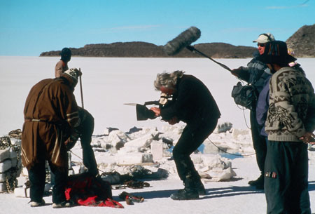 A crowd of people is standing around broken up chunkcs of salt with water under them. Peter- in the center wearing all black with gray hairs- is filiming people chaining the blocks together on the left of the image. You can't see one person because they are crouching behind another. The person in frot is wearing a long gray coat, blakc bants, and a brown and white har. Behidn this pair is someone in a brown jacket and something black covering their face. On the left is three people. Les is wearing a black jacket, sunglasses, and a white hat. He is holding a boom mic. There is someone in the middle of this crowd and all you can see is their purple jacket. The other person is wearing a brown and gray jacket, blakc pants, and a red/green/black hat.