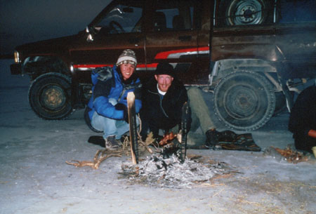 Tiffiny and Ken are crouching on the salt plains at night in front of a burnt out fire. The red truck is behidn them. Ken (on the right) is holding a cooked guinea pig. He is wearing a black jacket, pants, and hat. Tiffiny (on the left) is wearing a blue jacket, jeans, and a gray witner hat.