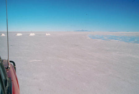 A picture taken out of the side of the red truck/SUV, you can see part of the hood on the bottom left corner. The car is driving over the salt. There are clumps ahead and water to the right. There is a hill in the far distance.