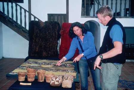 There is a large rectangular piece of fabric on a table and baskets as well as other artifacts on a table in front of the other one. Kate is pointing to the fabric and Ken is standing on the right. There are stairs in the background. As well as two large pieces of fabric hanging in front of the stairs- one is black and the other is red. Kate is wearing a blue jacket and jeans. She has a black bag over her shoulder. Her hair is brown and shoulder length. Ken is wearing a blue t shirt, a black vest, and khaki pants.