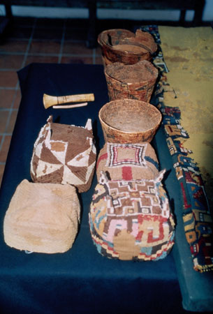 There is a table with a blue tablecloth. There are three round baskets, one square basket, three square cushion looking artifacts, and tools of some sort. You can see the corner of a large piece of fabric. There are colorful patterns on the edge and the rest in light brown.