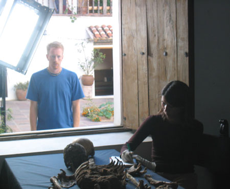 Ken is looking through a window at Tiffiny looking over an articulated skeleton. There is a light in front of the window. Ken is wearing a blue t shirt. He has short brown hair. Tiffiny is wearing a brown-ish shirt. She has shoulder length brown hair. She is wearing white gloves and writing something down.