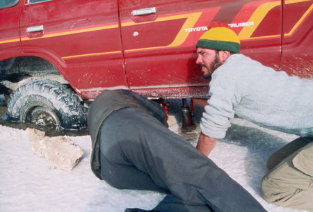 A close up of the red truck/SUV stuck in salt. There is a design along the bottom of the doors in yellow and red. A person in all gray is laying on the ground with their head and hands under the truck. Someone else in crouching on the ground. They are wearing a gray sweatshirt, khaki pants, and a green and yellow hat. They have brown facial hair.