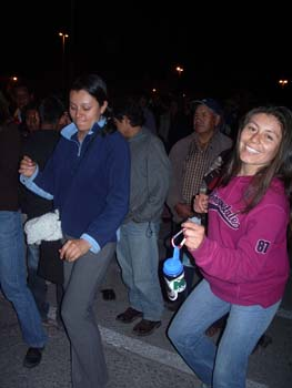 Sandra and Mirza dancing in a street in a crowd of people. It is night time and there are a few streetlights on the horizon. Sandra is wearing a navy jacket and light blue jacket. Her pants are gray and her black hair is in a bun. She is looking down and smiling at the ground. Mirza is smiling into the camera. She is wearing a purple sweatshirt with navy lettering and jeans. She is holding a water bottle with a light blue lid and a green and white sticker. She has shoulder length brown hair.