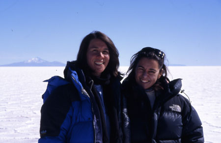 Tiffiny and Angela standing on the salt field. Tiffiny is on the left, wearing a blue jacket. She has shoulder length brown hair. Angela is wearing a black jacket and has sunglasses on her head. She has brown hair. They are both smiling into the camera.