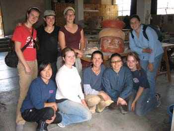 Cat, Ella, a person, Katie, Samantha, Tiffiny, Danielle (?), Emily, and someone else posing around a large ceramic hard. The face is red and it has a yellow and red helmet. Cat (left) is wearing a red tishirt and khaki pants. She has a brown bag crossed over one shoulder and a black bag over the other one. She has brown hair. Ella is wearing a black tshirt, black pants, and a gray hat. She has chin length brown hair. The next person in the back row- possibly Amy- is wearing a red shirt, jeans, glasses and a gray headband. In the first row Katie,