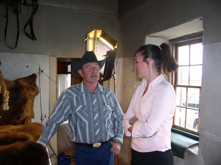 Heather (on the right) and another person are standing inside a house. The person on the left has their hand on a large piece of animal fur. They are wearing a blue, gray, and white stripped shirt. They also have jeans and a cowboy hat on. They have a gray mustache. The other person is wearing a pink shirt and black pants. Their brown hair is in a high pony tail. There is a large light behind them and a window.