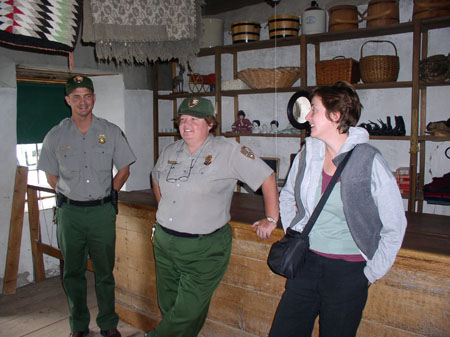 Ruth (on the right) and two other people are standing inside. There is a large wooden counter with wooden shelves behind them. There is baskets and other items on them. The person on the left and the one in the middle are wearing gray shirts, green pants, green baseball caps, and badges. Ruth is wearing a purple undershirt, a gray t shirt, and gray jacket. She has a black back over her shoulder. She has chin length brown hair. They are all smiling.
