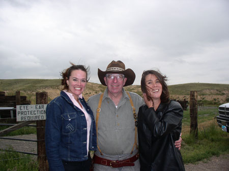 "Heather, Bill, and Tiffiny are outside. There are grassy hills behind them. It is windy. Heather is wearing a pink shirt and a denim jacket. Her brown hair in in a pony tail. Bill is wearing a green shirt, jeans, brown suspenders, gray glasses, and a brown cowboy hat. Tiffiny is wearing a black jacket. She is holding her brown hair out of her face. There is a sign on the fence behind them that reads ""eye + ear protection required."""