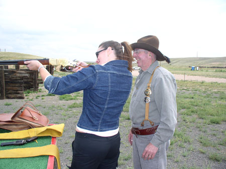 Heather and Bill are standing on a grassy field. Heather (left) is holding a rifle. Bill is standing behind her, smiling. She is smiling in front of her. Heather is wearing a pink shirt, a jean jacket., black pants, and sunglasses. Bill is wearing a green shirt, gray pants, brown suspenders, a green cowboy hat, and two badges.