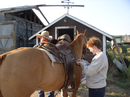 Three people are putting a saddle on a brown horse. The person on the left is wearing a light gray cowboy hat and has gray glasses. You can only see the legs of the person in the middle. The person on the left is wearing a creme sweatshirt and jeans. They have short red-ish brown curly hair.