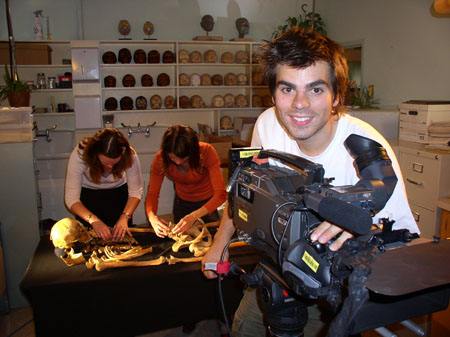 Heather and Tiffiny are laying out a skeleton on a black cloth covered table. They are looking down. There is a person in front of them setting up a camera. They are smiling into the camera taking the photo. They are wearing a white shirt and have messy brown hair. There are white shelves with skulls in the background. Heather (left) is wearing a white lone sleeved shirt and black pants. She has shoulder length brown hair. Tiffiny is wearing an orange longsleeved shirt and black pants. She has shoulder length brown hair.