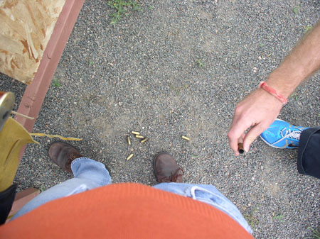 A shot of yellow bullet casings on the ground. The ground is gravel. You can see a brown bar with a piece of wood attached to it. There are two pairs of feet. The ones on the left are wearing brown shoes, jeans, and an orange shirt. On the right, there is one blue shoes, the bottom of black pants, and a hand with an pink-ish bracelet holding a shell casing.