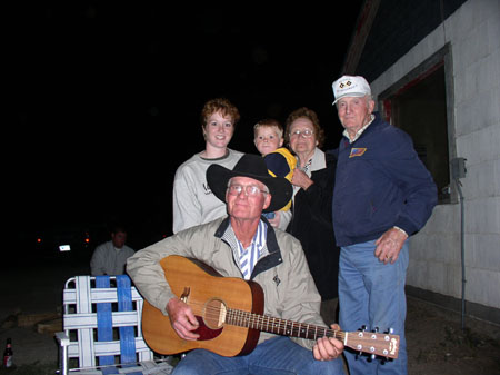 There are four adults and a child outside at night. Every one but the child is smiling into the camera. There is a white wall on the right with a rectangular opening that has a gray rim. In front, there's a person sitting in a chair holding a guitar. There are wearing a blue and white striped shirt, a light brown jacket, jeans, glasses, and a black cowboy hat. There is a blue and white lawn chair to their left. Behind them on the far left is a person with a gray sweatshirt, short red/brown hair, and small hoop earrings. They are holding a child with a blue and yellow jacket as well as blonde hair. Next to the child is a person wearing a black jacket with a gray collar. They are wearing glasses and have short brown hair. Their hand is on the child. On the right, is a person wearing a blue jacket with an american flag on it, jeans, and a white baseball cap. In the back, is a person sitting with a gray jacket. You can't see their face. There are taillights and an illuminated license plate.