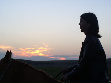 Tiffiny's silhouette on a horse. The sun is starting to set and the clouds in the background are pink and purple.
