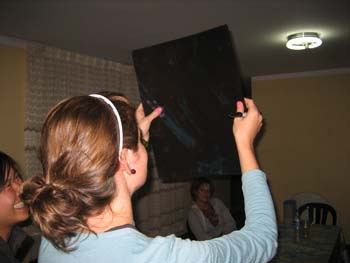 Cat and Katie are looking at xray of a pelvis. Cat's back is to the camera, but you can see Katie's face in the bottom left corner. There is someone sitting a table by white and brown curtains looking at them. Cat is wearing a blue jacket and a white headband. Her brown hair is in a ponytail. Katie is wearing a gray jacket and her black hair is pulled back. The person in the back is wearing a redish shirt and a white jacket.