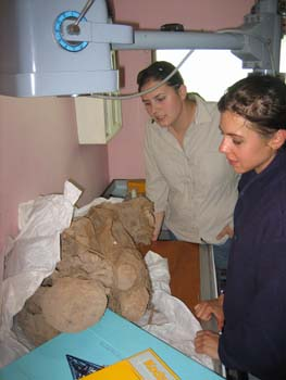 Ellen and Ella observing a mummy about to be x-rayed. The mummy is in the fetal position on a table. Ellen is wearing a beige long-sleeved shirt, jeans, and sunglasses on her head. Her brown hair is pulled back. Ella is wearing a navy shirt and her dark hair is pulled back.