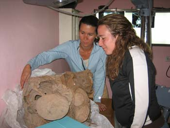 Tung and Rachel are observing a mummy about to be x-rayed. It is curled into a fetal position. Tiffiny is wearing a blue jacket, a white shirt, and khaki pants. Her brown hair is in a ponytail. Rachel is wearing a black jacket with a white stripe down the side. She has brown curly hair.