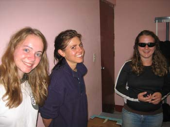 Emily, Ella, and Rachel are standing in the x-ray room. They are all smiling into the camera. The walls are pink. Emily is wearing a white tshirt with a black collar and an 8-ball on the right side of the shirt. She has long brown hair. Ella is wearing a navy shirt and her dark hair is in a ponytail. Rachel is wearing a black jacket with white stripes down the side, jeans, and sunglasses. She has long curly brown hair.