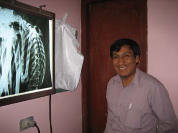 The lab tech is smiling is smiling at the camera in front on and x-ray of a mummy in a tight fetal position. The tech si wearing a red long sleeved shirt and black pants. Their hair and mustache are black.