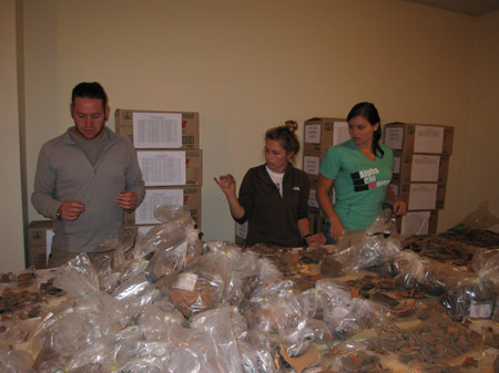 Alex, Emily, and CArol, are standing at a table covered in ceramic fragments and bags full of ceramic fragments. Alex is looking at the table, and Emily and Carol are looking at what he's holding. There are three stacks of cardboard boxes with white labels on both visible sides against the back yellow wall. Alex is wearing a gray shirt, gray jacket, khaki pants, and black sunglasses on his head. His brown hair is pulled back and he has brown facial hair. Emily is wearing a white tshirt and a black jacket. Her light brown hair is in a bun on her head. Carol is wearing a green tshirt with white letters on it. Her dark hair is in a ponytail.