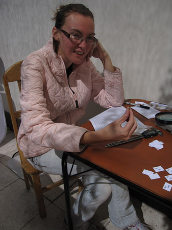 Alysha is holding up a tooth and smiling into the camera. There is a printed out spreadsheet and a gray ruler on the table in front of her on a wooden table. There is a pile of small white papers and some are laying separately with writing on them. The wall is white and so are the tiles on the floor. Alysha is wearing a pink jacket, gray pants, and glasses. Her brown hair is pulled back.