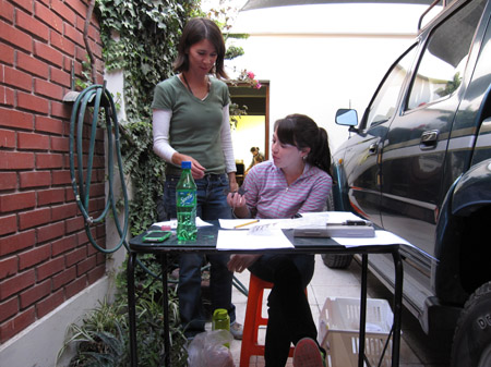 Tiffint and Allison are looking at a mandible that Alyson is holding. Alyson is sitting at a small black table outside The table has several papers on it, a green bottle of Sprite, and a phone. On the left of the photo there is a red brick wall with ivy on it and a green hose. There is a white wall in the background with an open door looking into inside- where a yellow light is shining and there is a silhouette of someone with a bun. On the right there is a black car. Tiffiny is wearing a white long sleeved shirt, a green tishirt, and jeans. Alyson is wearing a light purple and dark purple striped hoodie as well as jeans. Her brown hair is in a ponytail.