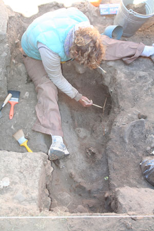 Amy- with brown and blonde curly hair- sitting next to a deep rocky hole- excavating juvenile bones. She is looking down into it and using paint brushes.