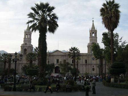 A long white building with two small towers on on either side is in the backgroud. There are people walking on the sidewalk in the foreground. There are tall tress that are similar to palm trees. This photo was taken in the Arequipa Plaza.