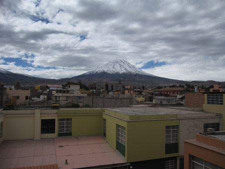 In the background there is a large volcano covered in snow at the top. There are large fluffy clouds covering the majority of the blue sky.There are several flat topped buildings that are yellow, red, and brown.