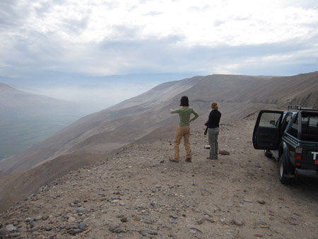 Tiffiny and Beth are standing on a flat rocky land overlooking a valley. Tiffiny is gesturing out. Behind the duo is a black SUV with its driver's door open. There is mist filling the valley. The blue sky has large fluffy clouds. Tiffiny is wearing a white long sleeved shirt, a green tshirt, and khaki pants. She has shoulder length brown hair. Beth is wearing a black jacket and gray pants. Her blonde hair is in a bun.