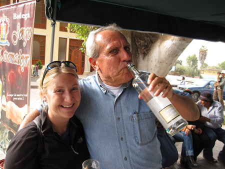 Beth is standing next to someone who has their arm around her- they are holding an empty glass alcohol bottle to their lips. They are standing under a black tent. They are both looking into the camera. Beth is wearing a black jacket, a black backpack, and black sunglasses on her head. The other person is wearing a white undershirt and jean shirt. They have short gray hair.