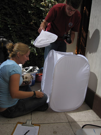 Beth and Sam are setting up to take a photo of a skull that Beth is holding. They are going to take the photo in a laundry hamper where the front and top have been cut out. The wall behind it is white and there are a lot leaves in the background. The ground is made of white square tiles. Sam is holding the top part of the laundry hamper and standing. Beth is sitting in front of it. She is wearing a blue tshirt and black pants. Sam is wearing a red polo shirt, jeans, and glasses. Sam has short brown hair.