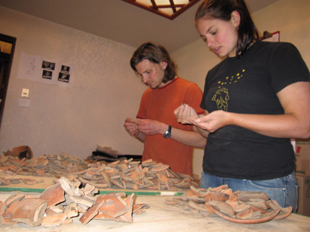 Brendan and Carol are sorting orange ceramic shards on a brown table. They are both looking at shards in their individual hands. The wall is yellow behind them. Brendan is wearing a red tshirt and a black watch. He has chin length brown hair and a brown mustache. Carol is wearing a black t shirt with yellow stars and a design on it as well as jeans. Her dark hair is in a ponytail.