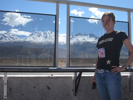 Carol is standing by windows with a view of mountains and is smiling to the left of the camera. The mountains are covered with snow. There is flat rocky ground covered with shrubs as well as asphalt between the windows and the mountains. The windows make up the majority of white frames attached to cement. Carol i swearing a black shirt with Vanderbilt written in yellow letters with a white outline across the front and the Vanderbilt logo- a golden star with a white outline and white V- on the bottom right. Her red, white, and blue wallet is around her neck on a black string. She is wearing jeans. Her brown hair is pulled back and a