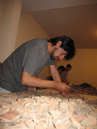 Abel is leaning over a wooden table covered in orange and brown ceramic shards. One of his hands is on the table and the other is holding a shard in his other hand.There are two people in the back ground working on an entirely different pile. The walls are yellow and the ceiling is white. Abel is wearing a gray tshirt and jeans. He has black chin length hair and beard.