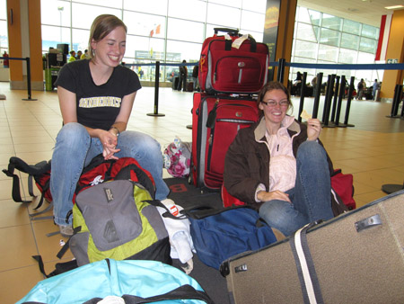 """Carol and Alysha are sitting on the ground in the airport surrounded by luggage. The are both smiling towards the right of the photo. There is a blue bag and a light brown suitcase in the foreground; a green backpack, a white jacket, and a blue duffel bag between the two people; and a red suitcase behind Alysha. There are black posts with fabric between them a few feet behind the red suitcase. A multiple feet behind that are large windows with rectangular panes divided by silver pieces of metal. There are yellow posts between every six columns. There are various groups of people by the windows. The floor is made of yellow tiles. Carol is wearing a black tshirt with gold letters with a white outline that reads """"Vanderbilt"""" as well as jeans. Her brown hair is pulled back. Alysha is wearing a pink jacket, a brown jacket, glasses, and jeans. Her brown hair is pulled back."""
