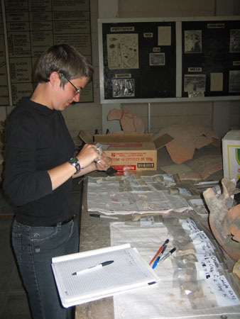 Chris is standing at a a table with teeth and bones in clear plastic bags. Chris is measuring something. Chris is wearing a black long sleeved shirt, dark jeans, glasses, and short brown hair.