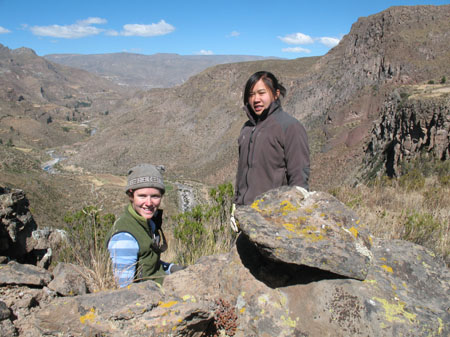Catherine- wearing a blue striped shirt, green vest, and gray beanie- and Katie- wearing a gray jacket and her brown hair is in a ponytail- standing behind rocks. There are two mountains behind them and a river in the valley.
