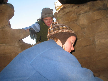 Cat and Rachel in the underground hole. Cat is in the opening looking down into the camera. Rachel is in the hole facing right. The walls are laid brown stones. Cat is wearing a light and dark blue striped shirt, green vest, black gloves, and a gray winter hat. Rachel is wearing a blue jacket and brown winter hat.