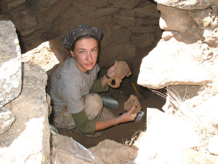 Sylvia is sitting in a hole with laid brown stone around it. She is holding a pelvis in one hand a sacrum in the other. She is wearing a gray tshirt, green long sleeved shirt, khaki pants, and a gray bandana. She is covered in dirt.